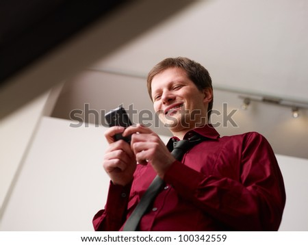mid adult business man in office, text messaging on mobile phone. Low angle view - stock photo