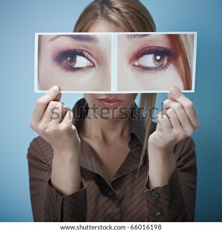 mid adult business woman holding photo of her eyes looking at different sides on blue background. Square shape, front view, waist up