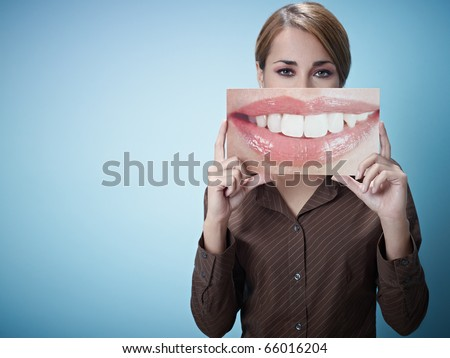 mid adult business woman holding photo of toothy smile on blue background. Horizontal shape, front view, waist up, copy space