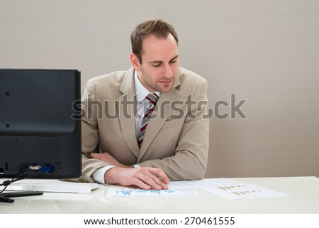 Mid Adult Businessman Analyzing Graph At Desk In Office - stock photo