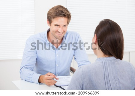 Mid adult businessman checking resume of female candidate during meeting in office - stock photo