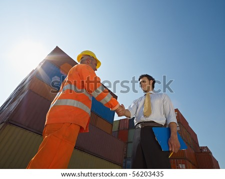 Mid adult businessman holding clipboard and shaking hands to manual worker near cargo containers. Horizontal shape, low angle view. Copy space - stock photo