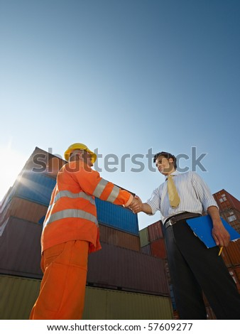 Mid adult businessman holding clipboard and shaking hands to manual worker near cargo containers. Vertical shape, low angle view. Copy space - stock photo