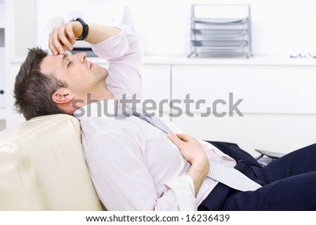 Mid-adult businessman lying on couch at office, looking exhausted eyes closed. Bright background.