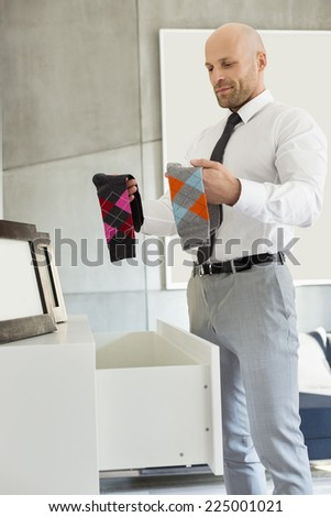 Mid adult businessman selecting socks at home