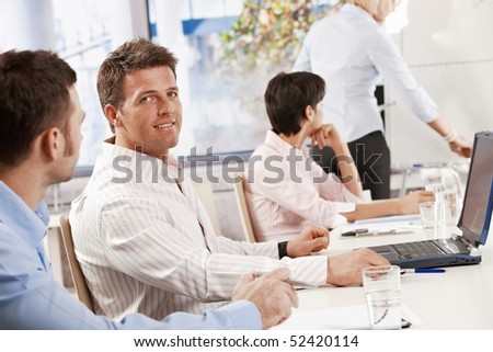 Mid-adult businessman sitting on business meeting with colleagues at office, looking at camera, smiling. - stock photo