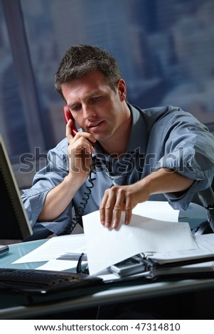 Mid-adult businessman speaking on landline phone working overtime in office checking papers. - stock photo