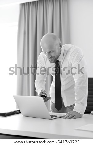 Mid adult businessman using call phone and laptop at table in home office