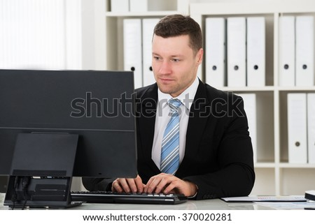 Mid adult businessman using computer at desk in office