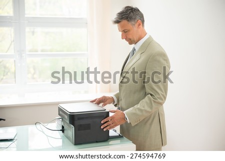 Mid-adult Businessman Using Photocopy Machine In Office - stock photo