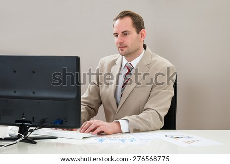 Mid Adult Businessman Working On Computer At Workplace - stock photo