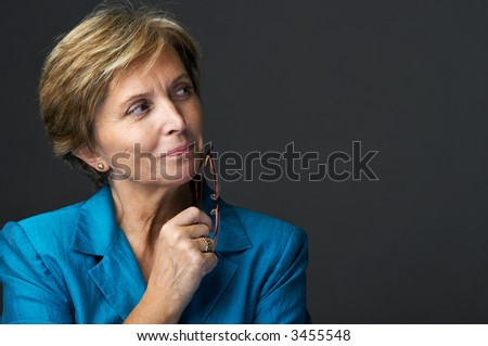 Mid adult businesswoman holding glasses and looking sidewards. - stock photo