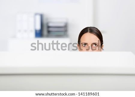 Mid adult businesswoman looking up in office cubicle - stock photo