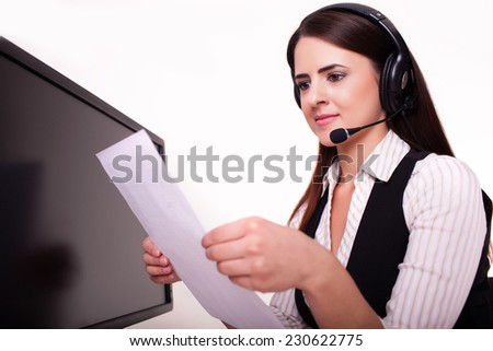 Mid adult businesswoman reading documents at office desk