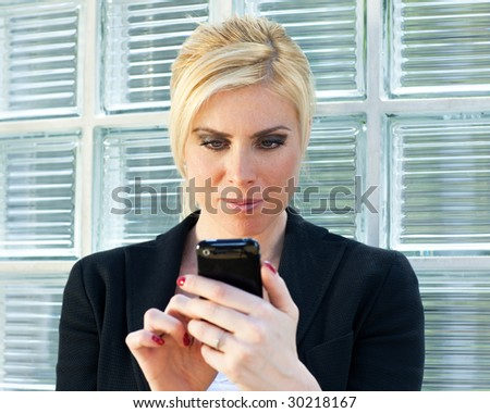 mid adult businesswoman reading phone message on smartphone. - stock photo