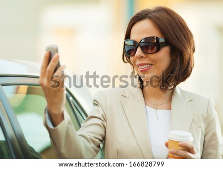 Mid adult businesswoman using smart phone outdoors. - stock photo