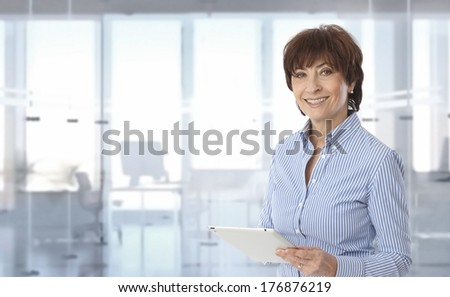 Mid-adult businesswoman using tablet computer at office. - stock photo