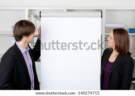 Mid adult businesswoman with male coworker looking at flip chart in office - stock photo