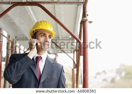 mid adult caucasian architect talking on telephone in construction site. Horizontal shape, front view, copy space - stock photo