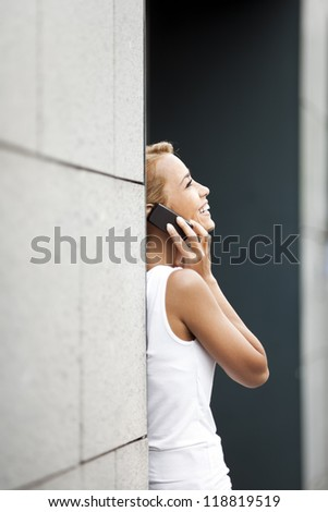 mid adult caucasian business woman talking on mobile phone and leaning on wall near office building. Copy space - stock photo