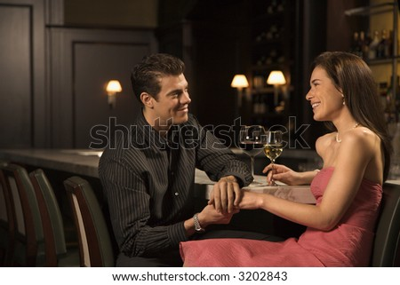 Mid adult Caucasian couple at bar holding hands and smiling. - stock photo
