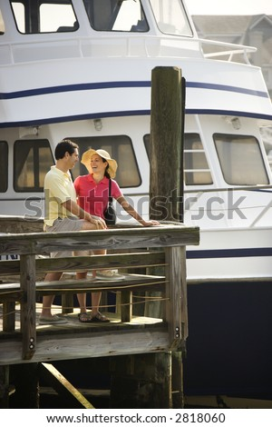 Mid-adult Caucasian couple at dock looking at each other with boat in background. - stock photo