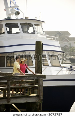 Mid-adult Caucasian couple at dock with boat in background.