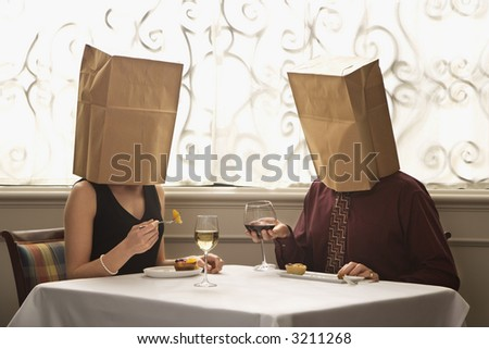 Mid adult Caucasian couple dining in a restaurant with paper bags over heads. - stock photo