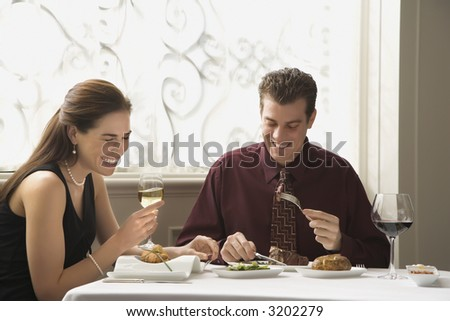 Mid adult Caucasian couple dining in restaurant and laughing. - stock photo