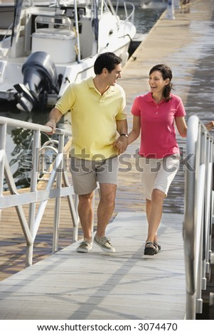Mid-adult Caucasian couple holding hands and walking up ramp at harbor.