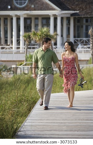 Mid-adult Caucasian couple holding hands walking down wooden trail.