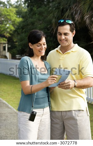 Mid-adult Caucasian couple holding map and smiling.