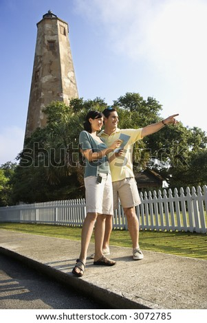Mid-adult Caucasian couple sightseeing with lighthouse in background at Bald Head Island, North Carolina. - stock photo