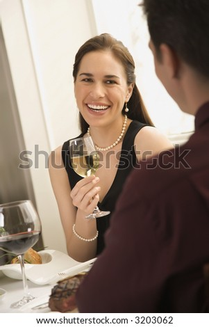Mid adult Caucasian couple smiling and drinking wine and dining. - stock photo
