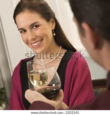 Mid adult Caucasian couple smiling and toasting wine glasses. - stock photo
