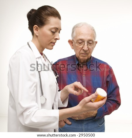 Mid-adult Caucasian female doctor pointing at prescription bottle as elderly Caucasian male looks at bottle. - stock photo