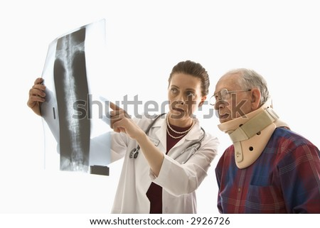 Mid-adult Caucasian female doctor ponting at x-ray with elderly Caucasian male in neck brace looks on. - stock photo