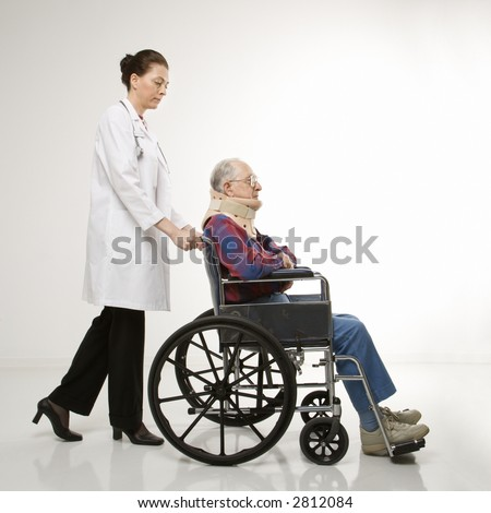 Mid-adult Caucasian female doctor pushing elderly Caucasian male with neck brace in wheelchair. - stock photo