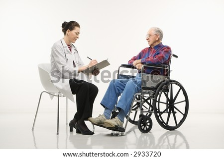 Mid-adult Caucasian female doctor taking notes with an elderly Caucasian male in wheelchair to her side. - stock photo