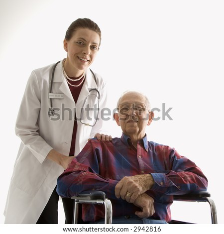 Mid-adult Caucasian female doctor with hands on elderly Caucasian male's shoulder in wheelchair. - stock photo