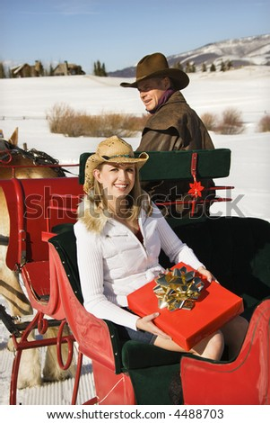 Mid-adult Caucasian female holding a present while sitting in a sleigh.