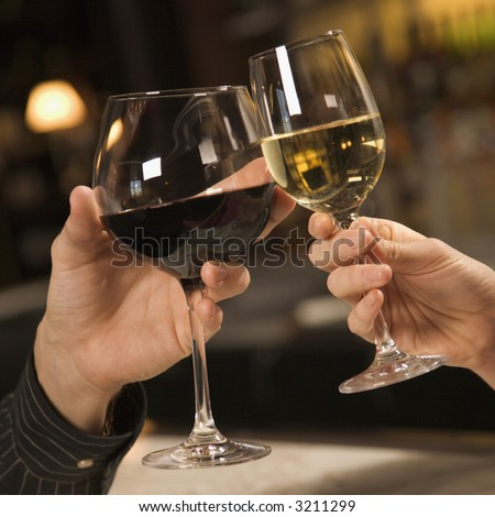 Mid adult Caucasian male and female hands toasting wine glasses. - stock photo