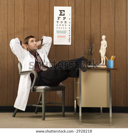Mid-adult Caucasian male doctor at desk reclining with hands behind head and feet on desk. - stock photo