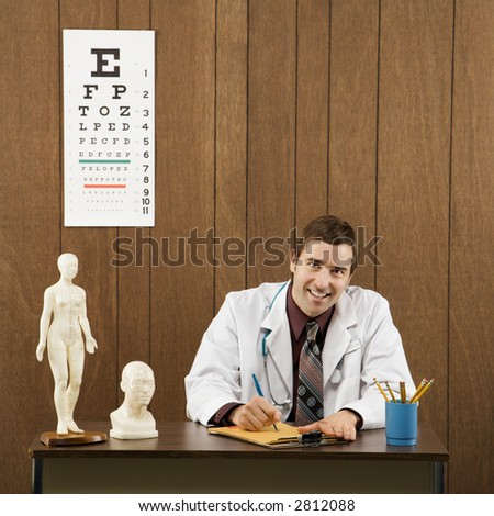 Mid-adult Caucasian male doctor sitting at desk writing and looking at viewer.