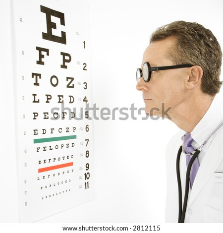 Mid-adult Caucasian male doctor wearing eyeglasses looking at an eye chart.