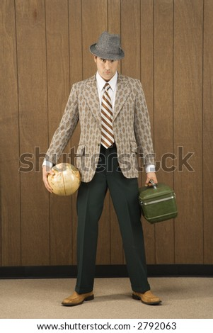 Mid-adult Caucasian male holding a globe and carrying luggage.