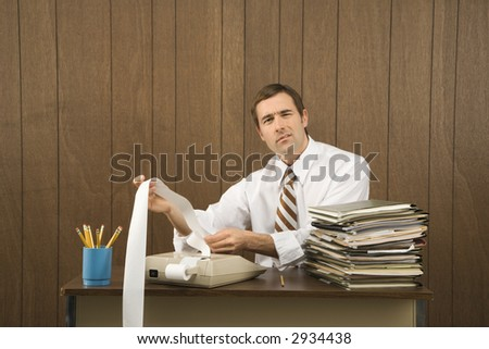 Mid-adult Caucasian male holding printout from calculator in office setting.