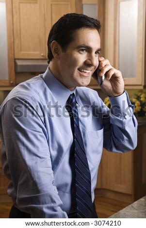 Mid-adult Caucasian male smiling and holding cell phone while standing in kitchen.