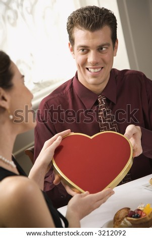 Mid adult Caucasian man giving a heart shaped box of chocolates to surprised woman at restaurant. - stock photo