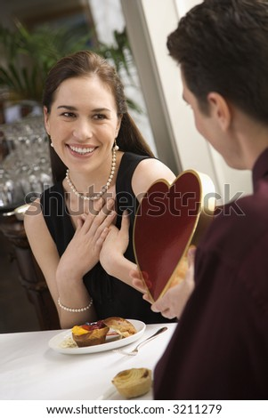 Mid adult Caucasian man giving a heart shaped box of chocolates to woman at restaurant. - stock photo